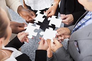 Close-up Photo Of Businesspeople Holding Jigsaw Puzzle